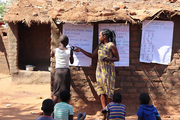 Temwa Chilenga teaching under difficult conditions