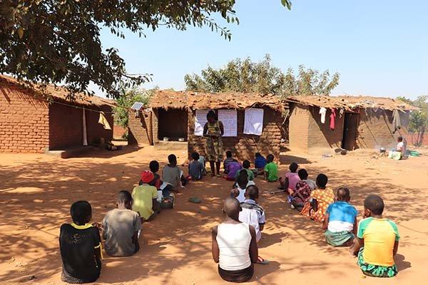 A classroom set up under a tree shelter